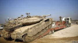 An Israeli soldier directs a tank onto a truck for transport near the border with Gaza August 6, 2014