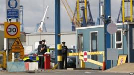 Policemen stand guard at an entrance to Tilbury Docks