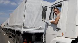 A truck driver looks out of the cabin of his vehicle which forms part of an aid convoy destined for Ukraine