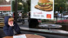A woman sits a table of a closed McDonald