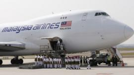 Soldiers carry a coffin as it leaves the plane