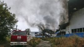 A fire engine is parked next to burning printing factory hit by what locals say, was recent shelling by Ukrainian forces in Donetsk August 23, 2014