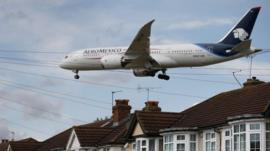 A passenger plane comes into land near housing at Heathrow Airport