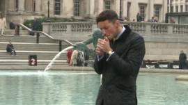 Man lighting cigarette in Trafalgar Square