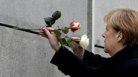 German Chancellor Angela Merkel places a rose at the Berlin Wall memorial in Bernauer Strasse