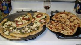Two pizzas sitting on top of a stove top oven