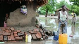 People outside flooded huts