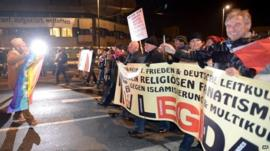 A counter demonstrator with a peace flag opposes the demonstration of Pegida