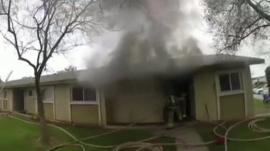 House with smoke billowing out and a fire fighter exiting