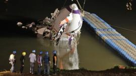 The wreckage of a TransAsia Airways turboprop ATR 72-600 aircraft is recovered from a river, in New Taipei City