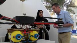 Sameera A. Almulla, Khalifa University stands next to a drone which can disperse fog
