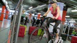 BBC Click's Lara Lewington rides a bicycle wearing a virtual reality headset