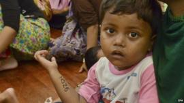Close up of a migrant girl from Myanmar in the arms of her mother in Malaysia