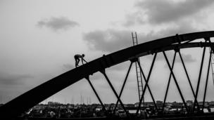 'Man on a bridge in Chittagong, Bangladesh' from the web at 'http://ichef.bbci.co.uk/news/304/cpsprodpb/0A48/production/_87223620_9_the_daredevil_by_ata_adnan.jpg'