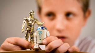 'A boy playing with two Star Wars figures' from the web at 'http://ichef.bbci.co.uk/news/304/cpsprodpb/1546/production/_86664450_edit-boy.jpg'