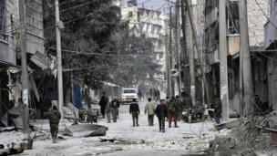 Syrian pro-government troops walk through the streets with civilians in eastern Aleppo, Syria, 12 December 2016