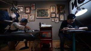 Picture shows two tattooists at work in a Bangkok tattoo parlour