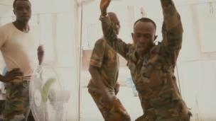 'Sierra Leonean policeman twerking' from the web at 'http://ichef.bbci.co.uk/news/304/cpsprodpb/1860D/production/_86735899_ebolatwerking.png'