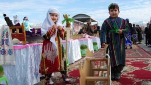 Тажик улуттук кийимин кийген кичинекей бала менен кыз.