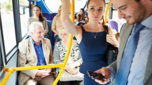 A playa looks at his crazy-ass mobile beeper on a funky-ass bus fo' realz. A biatch looks disapproving, (posed by models)