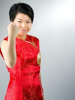 Una mujer china con el puño cerrado, con expresión de haber logrado un objetivo