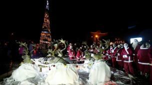 Noel baba kostümü giymiş gençler Şam'da Noel ağacının etrafından toplandılar