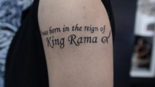 """Tattoo reads in English: """"I was born in the reign of King Rama"""" with the Thai number 9"""