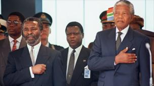 South Africa's new President Nelson Mandela (R) stands at attention as the national anthem is played during his inauguration
