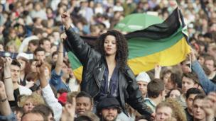 Music fans give the clenched fist and hold an African National Congress flag at Wembley Stadium, London, prior to the start of the Nelson Mandela Concert, April 16, 1990