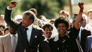 Nelson Mandela and wife Winnie, walking hand in hand, raise clenched fists upon his release from Victor prison, Cape Town, 11 February 1990