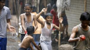Boys playing cricket in the rain in Mumbai