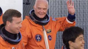 John Glenn waving and wearing his space gear