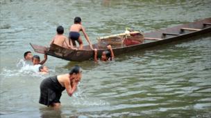 A woman takes a bath while children play in the Nam Tha river