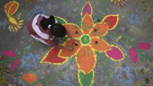 Girl painting a rangoli with different coloured powders
