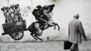 A man passes a cartoon on a wall in Milan mocking Silvio Berlusconi, 29 September 2011