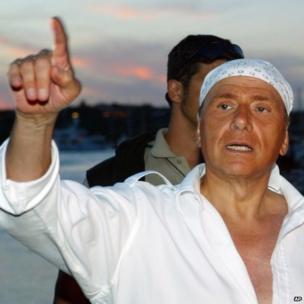 Silvio Berlusconi, a print bandanna on his head, in Sardinia, 16 August 2004