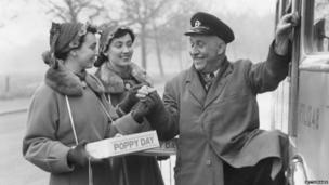 Black & white image of two female poppy sellers giving a poppy to a bus driver