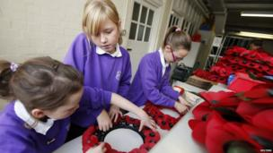 Children making poppy wreathes at factory