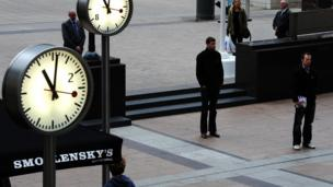 Clocks at showing 11.01am, beside people standing still.