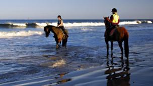 Women on horses on the seashore