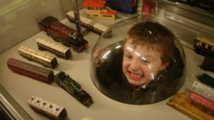 Boy with his head in a model trains museum exhibit