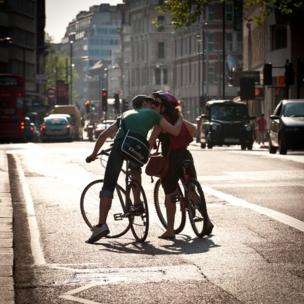 Cyclists exchange a kiss