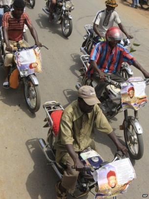 Men ride motorcycles bearing posters of Chukwuemeka Ojukwu