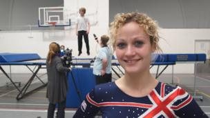 Miss Parker, a PE teacher who is ranked number one in the world for synchronised trampolining, poses in her gear as her students film their packages for School Report