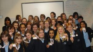 The School Report team at Rugby High School gather together and hold up their School Report passes