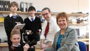 A student from The Community School of Auchterarder poses holding a camera before his fellow students and teachers