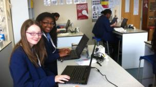 Our Lady's Convent High School Girls sit in front of their laptops and smile for the camera