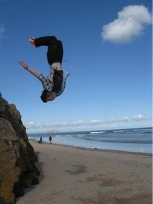 Man back-flipping off rocks