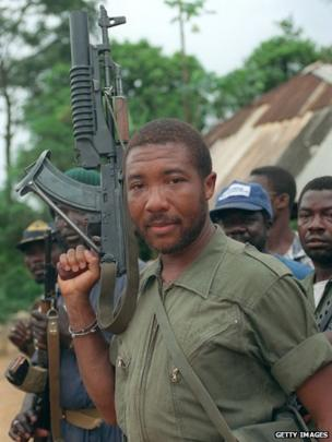 Charles Taylor holds his Soviet-made AK-47 assault rifle in Buchanan 29 May 1990 as he continues his march on the capital Monrovia to oust President Samuel Doe after a five-month-old insurgency.