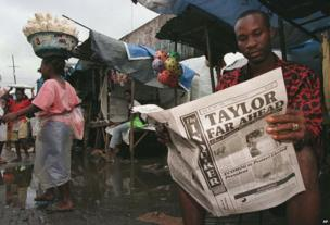 A Liberian man in the Monrovia market reads the city newspaper with preliminary election results showing warlord Charles Taylor leading 22 July 1997